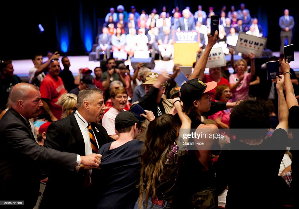 Protestors holding up copies of the Constitution are escorted out of Republican Presidential candidate Donald Trump's speech at the Merrill Auditorium on August 4, 2016 in Portland, Maine.