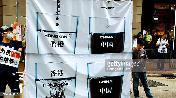 Protestors holds a banner with an anti-mainland Chinese illustration featuring a picture of a glass of water and a glass of ink, representing the...