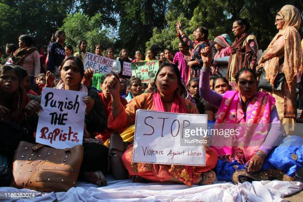 Protestors holds a placard and shout slogans during a sit-in protest as Delhi Commission for Women chief Swati Maliwal launched an indefinite hunger...