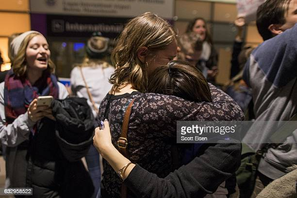 Protestors hug during a demonstration against the new ban on immigration issued by President Donald Trump at Logan International Airport on January...