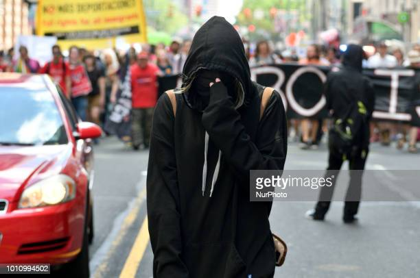 Protestors in black attire and covered face walks in front on an Abolish ICE march and rally in Center City Philadelphia PA on August 4 2018 After...