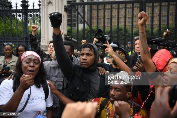 Protestors including British actor John Boyega raise their fists in Parliament square during an antiracism demonstration in London on June 3 after...