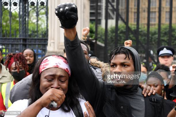 TOPSHOT Protestors including British actor John Boyega raise their fists in Parliament square during an antiracism demonstration in London on June 3...