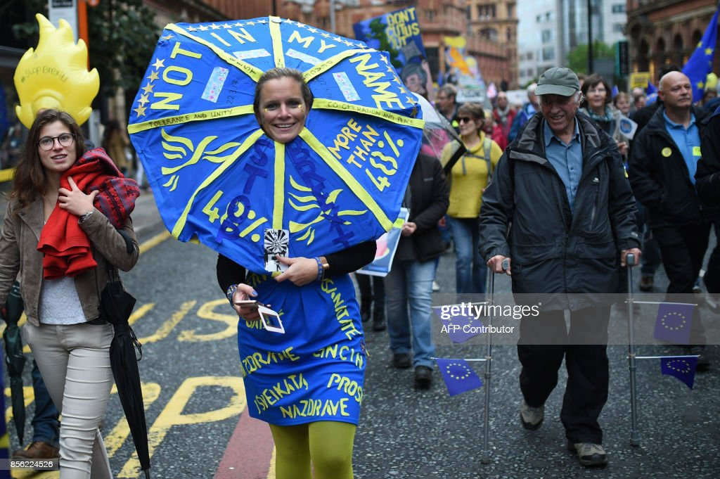 A protestors is bedecked in the EU colours during an anti-Brexit march on the first day of the Conservative Party annual conference in Manchester on October 1, 2017. British Prime Minister Theresa May's Conservative Party gathers on October 1, 2017, for its annual conference, dominated by questions about her leadership and splits on Brexit. / AFP PHOTO / Oli SCARFF
