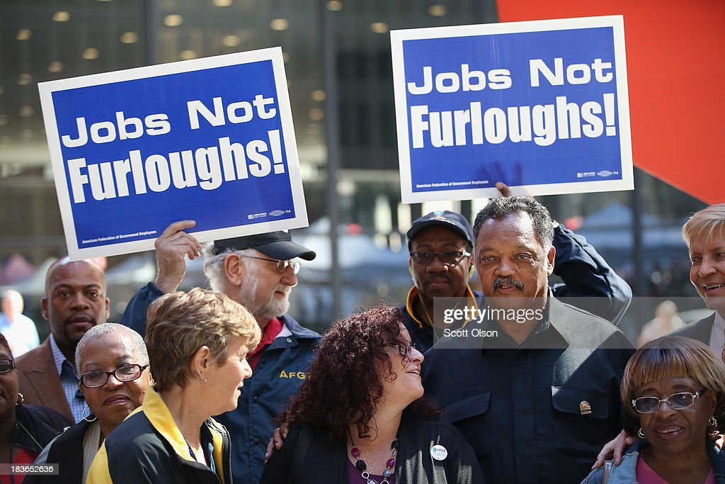 Protestors join Rev. Jesse Jackson (3rd R) during a march to call for an end to the federal government shutdown on October 8, 2013 in Chicago, Illinois. The protest was organized by the Rev. Jesse Jackson and the Rainbow PUSH Coalition as well as local labor, faith and community leaders.