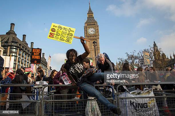 Protestors jump over barriers surrounding Parliament Square during a march against student university fees on November 19 2014 in London England A...