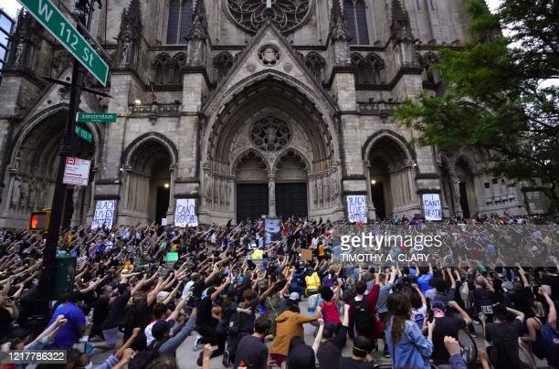 TOPSHOT Protestors kneel and raise theirs fists during a vigil at the Cathedral Church of St John the Divine in New York June 5 2020 against the...