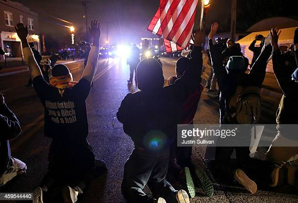 Protestors kneel with their hands up in front of police vehicles during a demonstration on November 24 2014 in Ferguson Missouri A St Louis County...