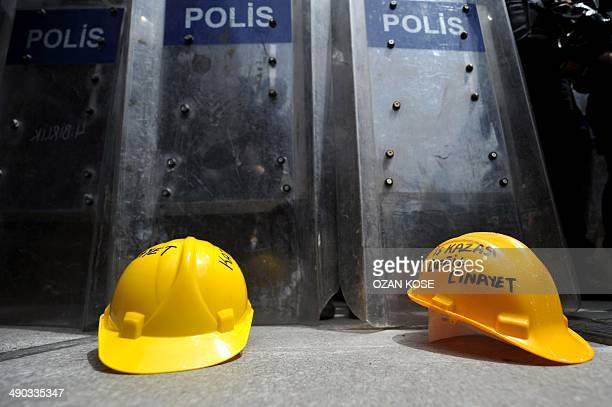 """Protestors leave miner helmets front of riot police shields """"not a industrial accident, murder"""" on May 14, 2014 in Istanbul.The Turkish government..."""