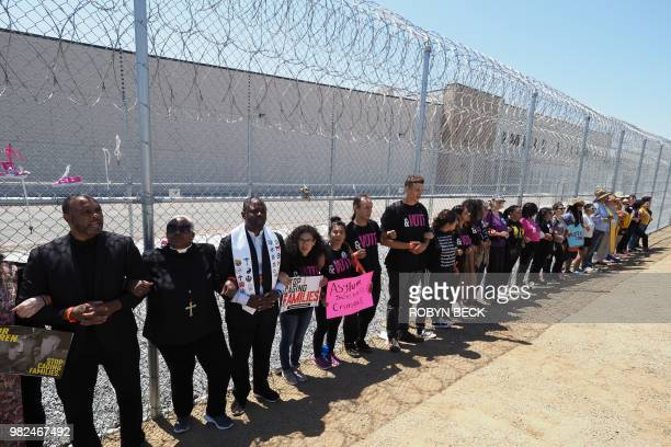 Protestors link arms after tying children's shoes and keys on the fence outside the Otay Mesa Detention Center during a demonstration against US...
