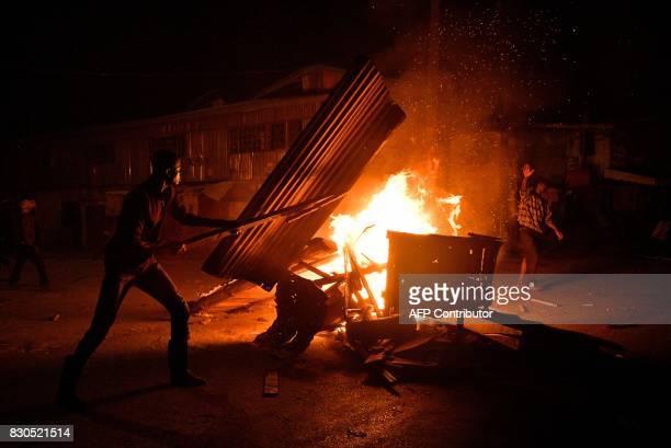 Protestors loot and burn premises belonging to the Kikuyu tribe on August 11 2017 in the Kibera slum of Nairobi Immediately after news broke that...