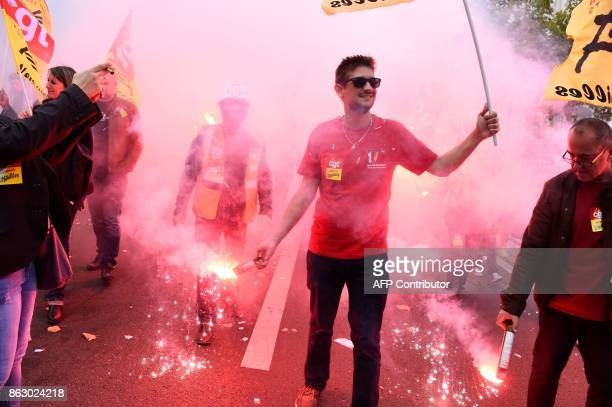 Protestors march as they hold lit flares during a demonstration called by the CGT workers' union in Paris on October 19 part of nationwide rallies...