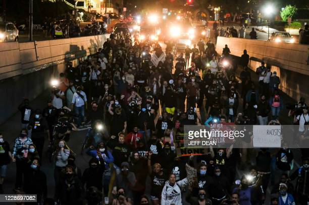 Protestors march as they protest the lack of criminal charges in the police killing of Breonna Taylor, in downtown Louisville, Kentucky on September...