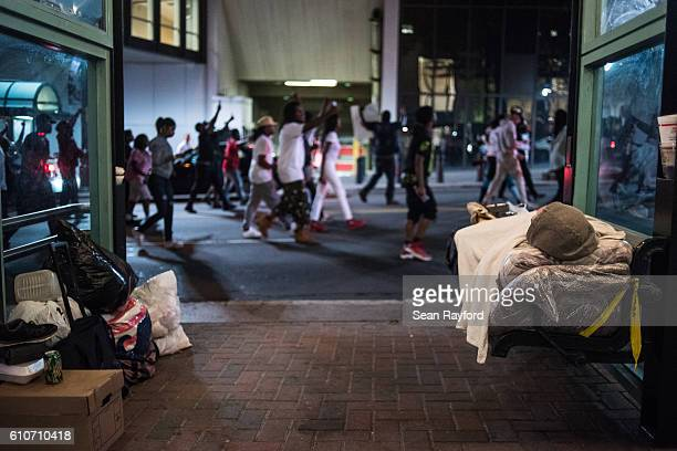 Protestors march by a homeless man September 21 2016 in uptown Charlotte North Carolina Protests in Charlotte began on Tuesday in response to the...