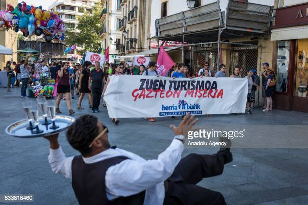 Protestors march during a demonstration against tourists as they hold a banner reading Your tourism is the misery for the young in San Sebastian...