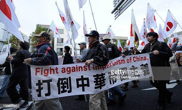 Protestors march holding Japanese national flags and a banner during a demonstration denouncing China during the AsiaPacific Economic Cooperation in...