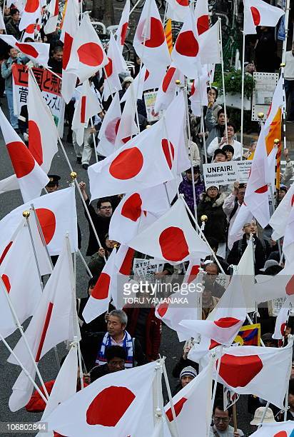 Protestors march holding Japanese national flags during a demonstration denouncing China during the AsiaPacific Economic Cooperation in Yokohama on...
