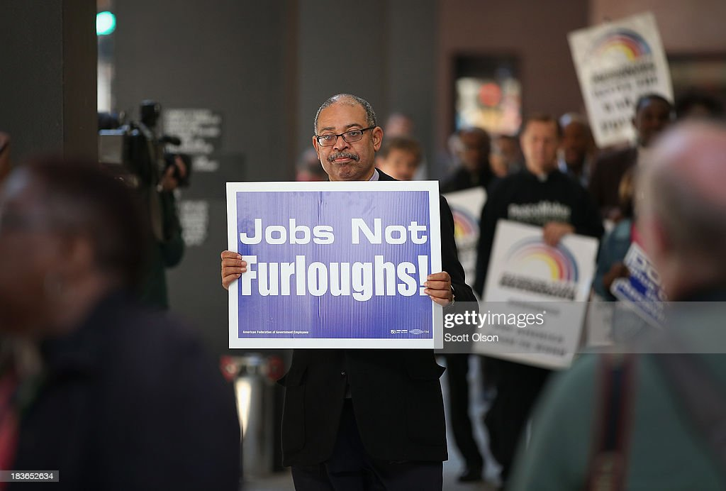 Protestors march in the Federal Building Plaza to call for an end to the federal government shutdown on October 8, 2013 in Chicago, Illinois. The protest was organized by the Rev. Jesse Jackson and the Rainbow PUSH Coalition as well as local labor, faith and community leaders.