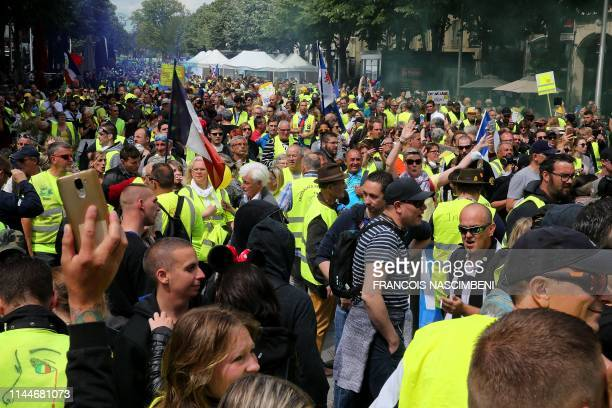 """Protestors march in the streets during a demonstration called by the """"Yellow Vests"""" movement on May 18, 2019 in Reims, eastern France, during the..."""