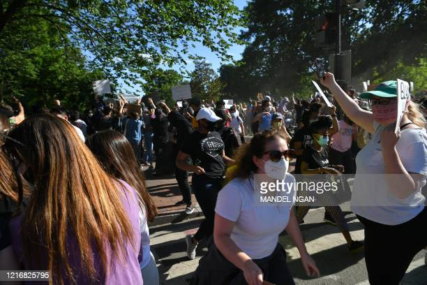 Protestors march on Lafayette Square near the White House in Washington DC on June 1 2020 Police fired tear gas outside the White House late Sunday...