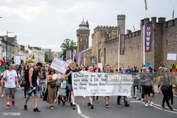 Protestors march past Cardiff Castle during a protest against vaccine passports on September 18, 2021 in Cardiff, Wales. First Minister of Wales Mark...