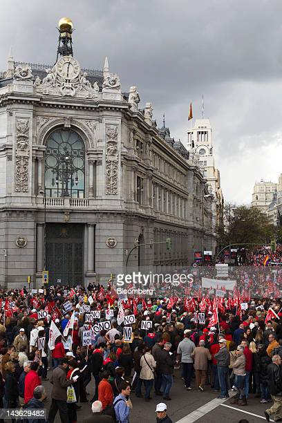 Protestors march past the headquarters of Spain's central bank, left, during a labor demonstration on May Day in Madrid, Spain, on Tuesday, May 1,...