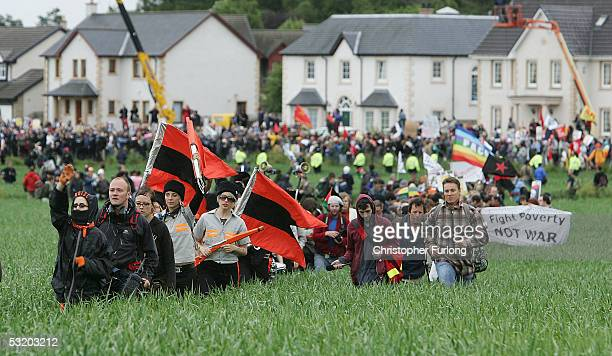 Protestors march through a field to the security fence surrounding the G8 summit on July 6, 2005 near Gleneagles, Scotland. The G8 summit where...