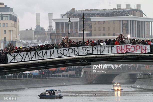 """Protestors occupy a bridge decorated with a banner reading """"Crooks, give us the election back,"""" across the Moskva River during a mass rally against..."""