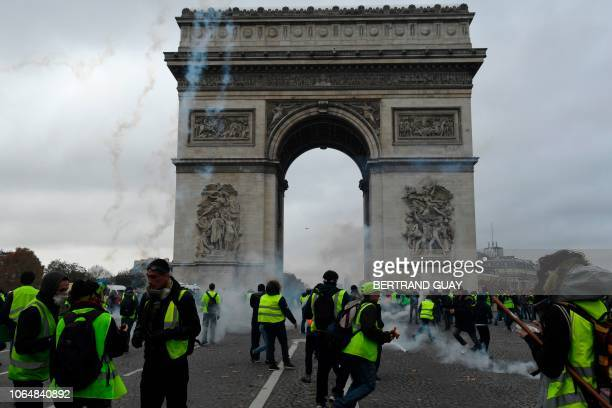Protestors of the yellow vest movement walk past the Arc of Triomphe on the Champs Elysees in Paris on November 24 2018 during a protest against...