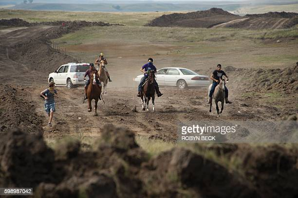 Protestors on horseback gallop away after members of the Standing Rock Sioux tribe and their supporters confronted a bulldozer crew and the private...