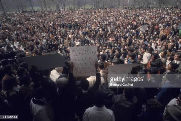 Protestors on stage hold up signs for the crowd at an antiwar demonstration at the bandshell in Central Park New York April 27 1968 One poster at...