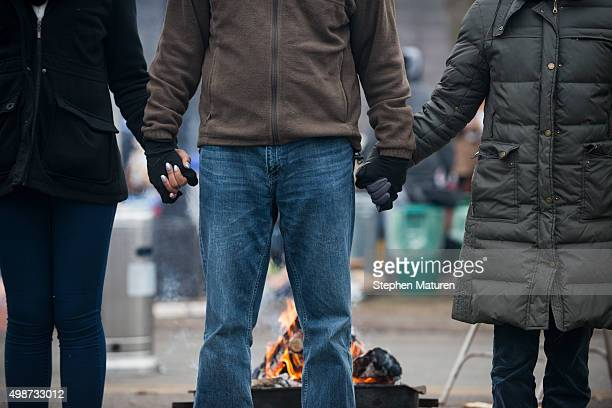 Protestors outside the 4th Precinct Minneapolis Police station hold hands awaiting the funeral procession for Jamar Clark on November 25 2015 in...
