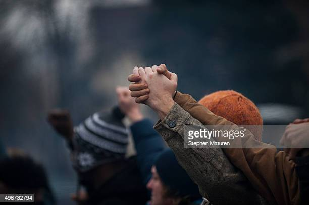 Protestors outside the 4th Precinct Minneapolis Police station raise their arms as the funeral procession for Jamar Clark passes by on November 25...