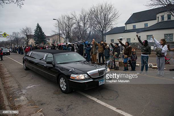 Protestors outside the 4th Precinct Minneapolis Police station raise their fists as the funeral procession for Jamar Clark passes by on November 25...