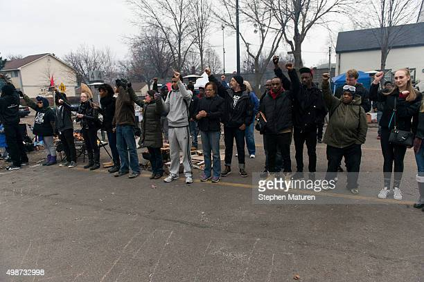 Protestors outside the 4th Precinct Minneapolis Police station raise their fists awaiting the funeral procession for Jamar Clark on November 25 2015...