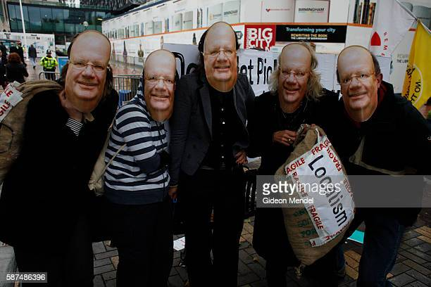 Protestors outside the Conservative Party Conference wear Eric Pickles masks He is the Communities Secretary in the cabinert and they were protesting...