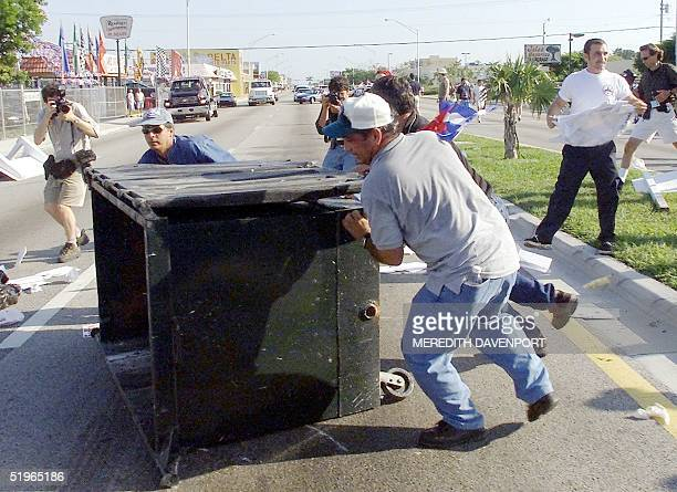 Protestors overturn a dumpster near the Miami home where Cuban shipwreck survivor Elian Gonzales had been staying with relatives in Miami 22 April...