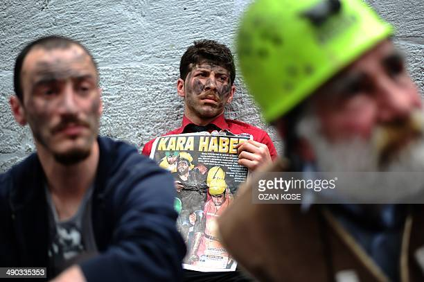 """Protestors paint their faces as miners and a hold a newspaper """"read: black news"""" at Istiklal Avenue on May 14, 2014 in Istanbul. The Turkish..."""