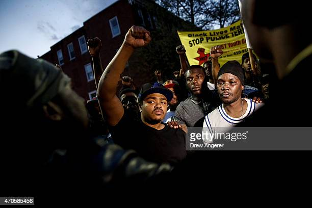 Protestors participate in a vigil for Freddie Gray down the street from the Baltimore Police Department's Western District police station April 21...