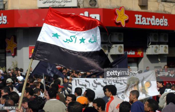 Protestors pass by Hardee's an American fastfood chain carrying an Iraqi flag during an antiUS demonstration March 20 2003 in Cairo Egypt The...
