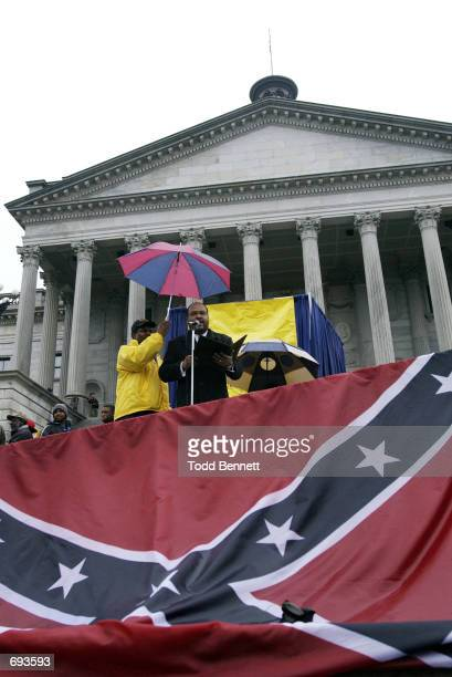 Protestors prepare to bury the Confederate flag January 21 2002 at the steps of the statehouse in Columbia SC as they call for the removal of the...
