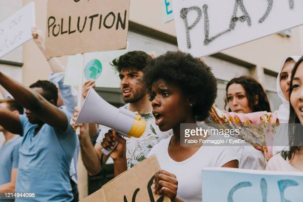 protestors protesting outdoors - demonstration stock pictures, royalty-free photos & images