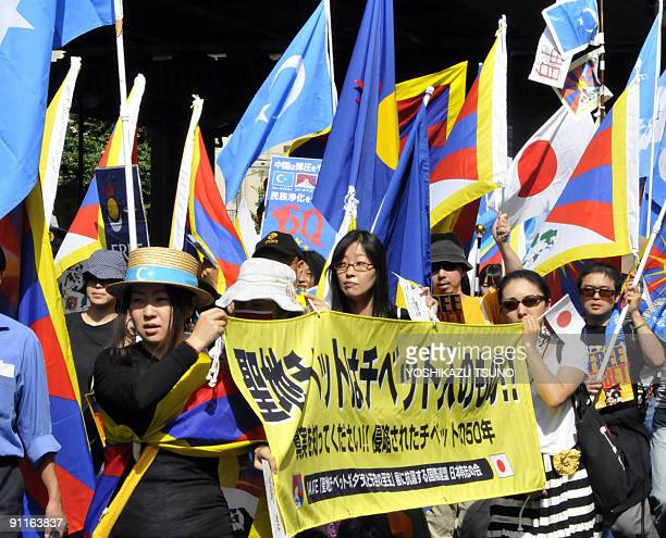 Protestors raise the flags of Tibet Japan and the 'East Turkestan' independence movement during an antiChina demonstration in Tokyo on September 26...