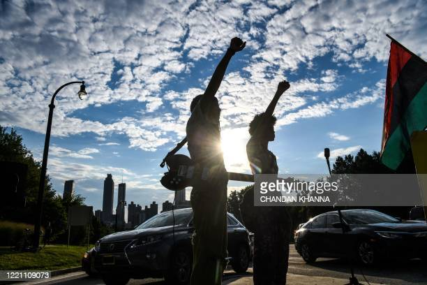 Protestors raise their fist during a protest to mark Juneteenth on June 19 in Atlanta, Georgia. - The US marks the end of slavery by celebrating...