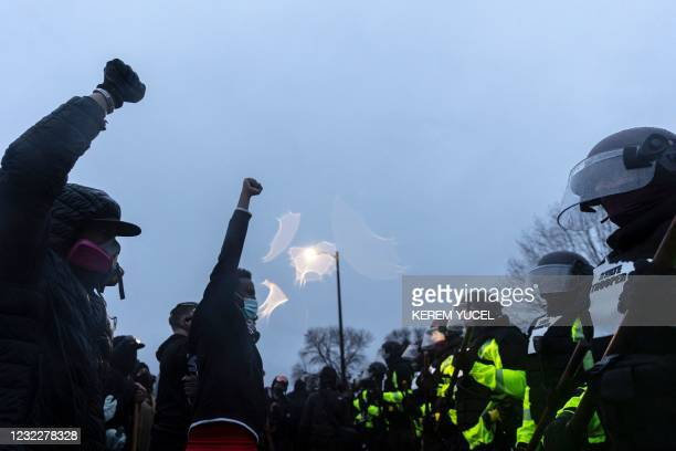 Protestors raise their fists as they face off with the Minnesota State Troopers standing guard outside the Brooklyn Center Police Station after a...
