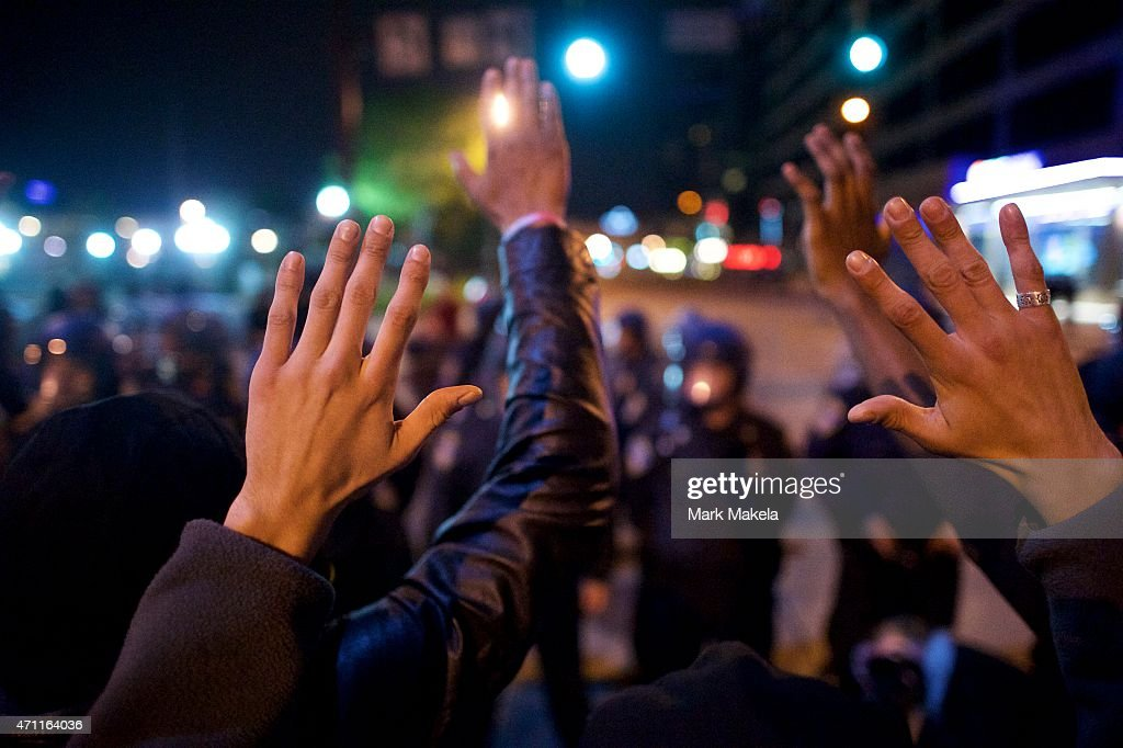 Protestors raise their hands as police in riot gear advance to force them off the street after a gathering in honor of Freddie Gray April 25, 2015 in Baltimore, Maryland. Freddie Gray, 25, was arrested for possessing a switch blade knife April 12 outside the Gilmor Houses housing project on Baltimore's west side. According to his attorney, Gray died a week later in the hospital from a severe spinal cord injury he received while in police custody.