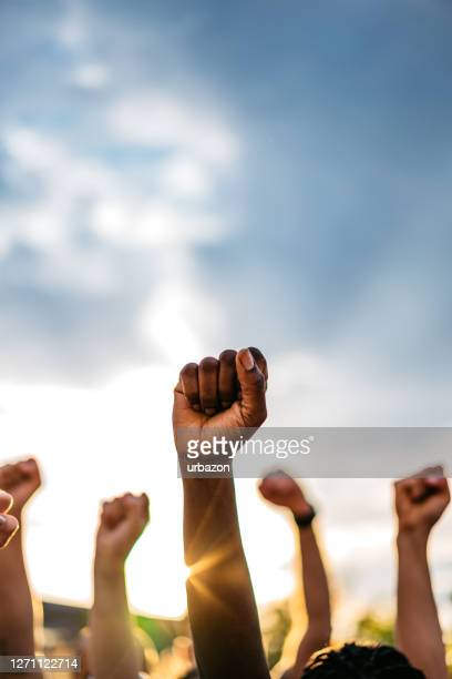 protestors raising fists - equality stock pictures, royalty-free photos & images