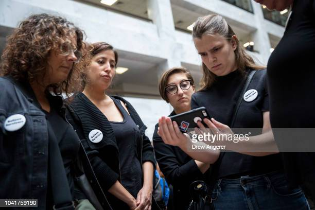 Protestors rallying against Supreme Court nominee Judge Brett Kavanaugh watch testimony from Christine Blasey Ford on a smartphone inside the Hart...