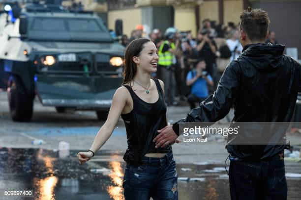 Protestors recover after being sprayed by police water cannons during the 'Welcome to Hell' anti-G20 protest march on July 6, 2017 in Hamburg,...
