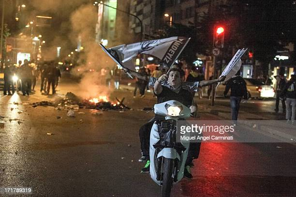 Protestors riding a scooter and waiving flags at Cumhurriyet Av. Near Taksim Square during the night riots.